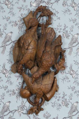 Trophée au canard, poule faisane et perdreau parmi des branchages de chêne, corne d'appel, gourde de chasse et fusil