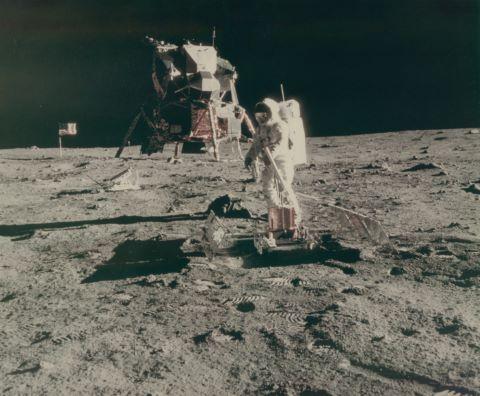 Rare très grand format. Aldrin se tient à côté du sismographe, le module lunaire et le drapeau américain en arrière-plan